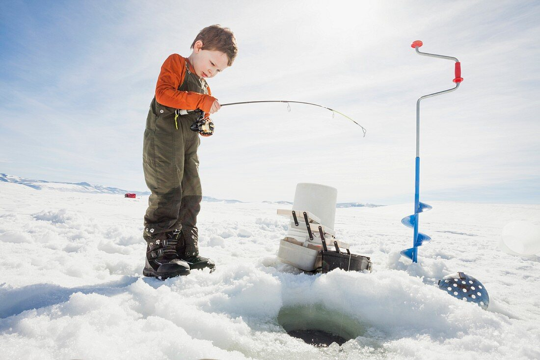A little boy ice fishing