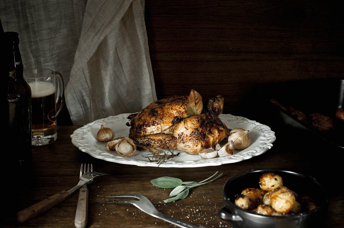 A whole roast chicken on a white plate with garlic, sage, beer and potatoes.