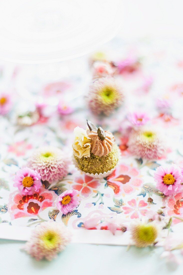 Pistachio confectionery decorated with flowers on a floral tablecloth