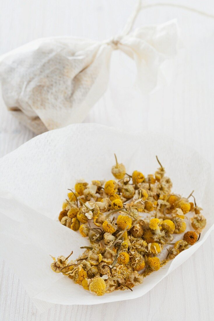 Client camomile flowers in teabags, one open and one tied