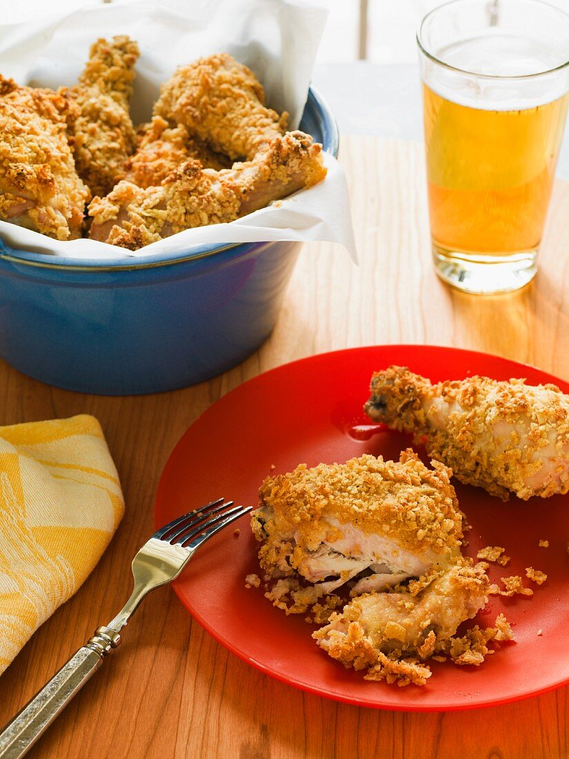 Fried chicken cut open on a red plate with a blue crock full of chicken and a beverage in the background