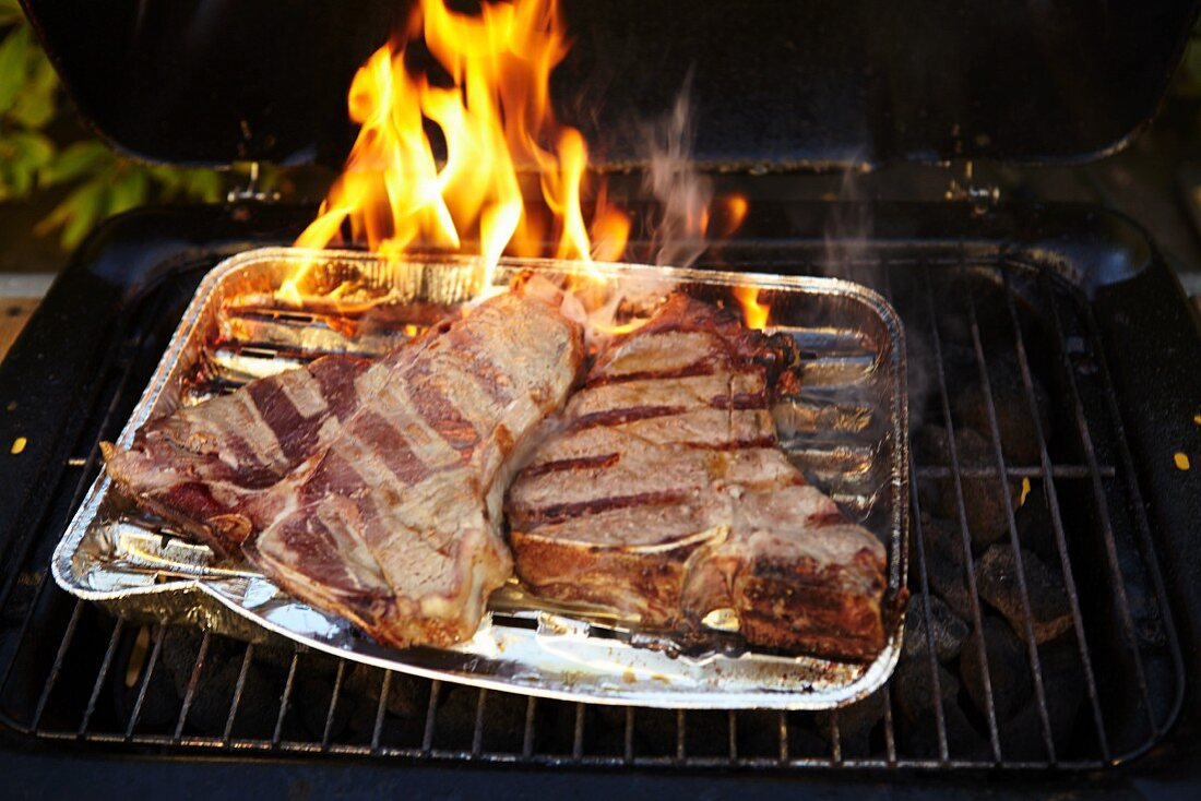 T-bone steaks in an aluminium tray on a barbecue