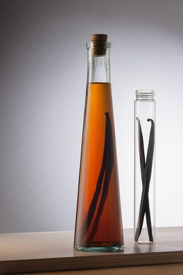 A bottle of vanilla extract and two vanilla pods in a glass tube