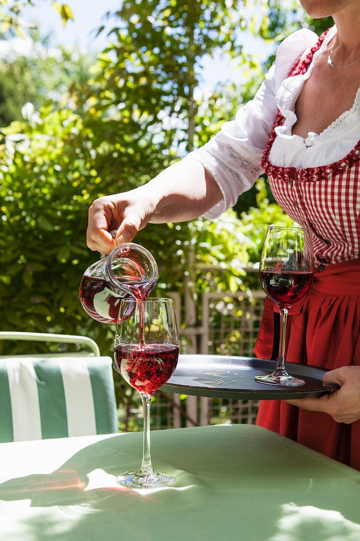 A woman pouring red wine into a glass on a garden table