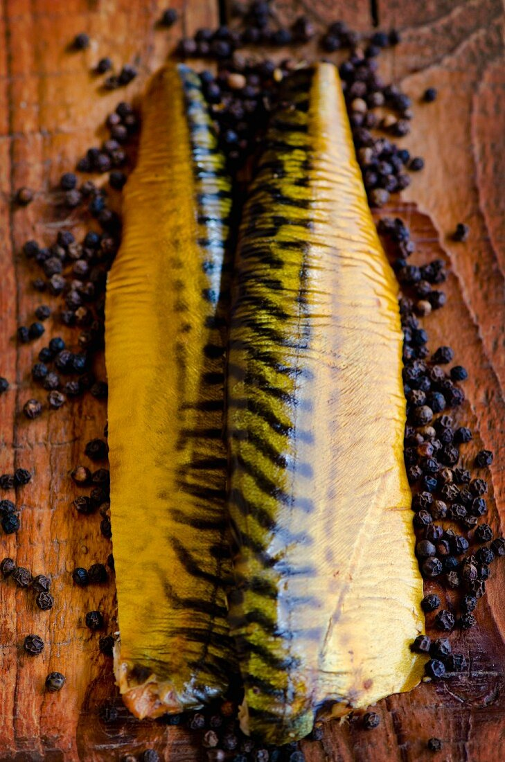 Smoked mackerel fillets on a pine wood board surrounded by peppercorns
