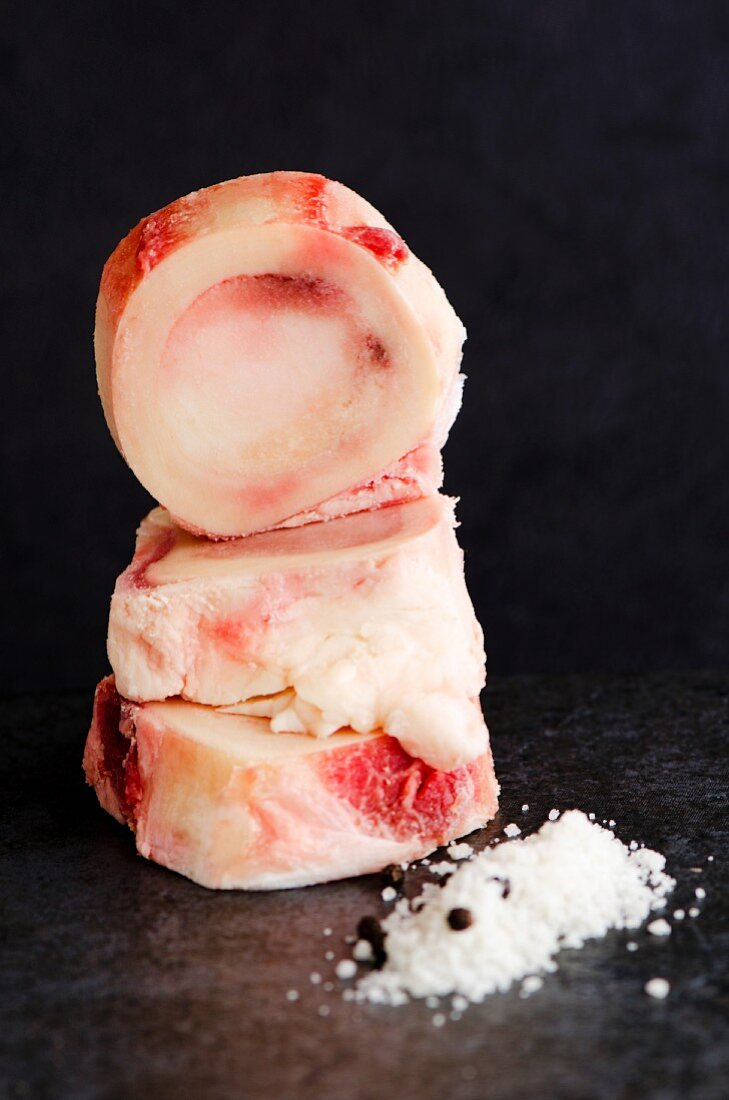 Stack of raw marrow bones next to a pile of Fleur de Sel and pepper