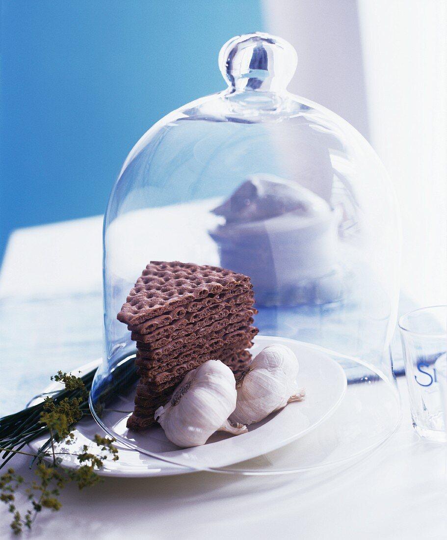 Crisp breads and garlic under a decorative glass cloche