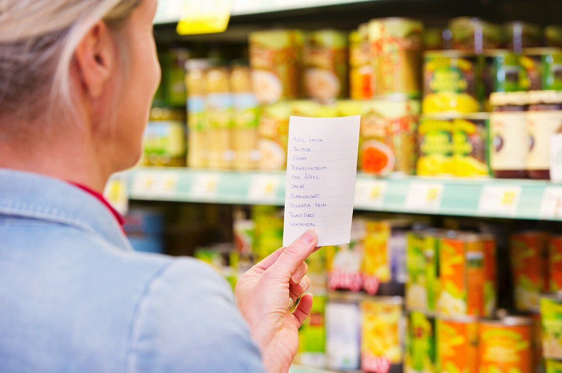 A woman with a shopping list in front of a shelf in a grocery store