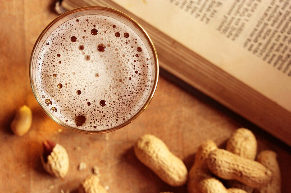 A glass of beer and peanuts next to an open book (seen from above)