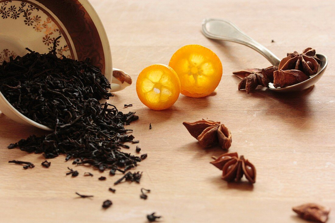 Black tea with anise stars and a kumquat on a wooden surface