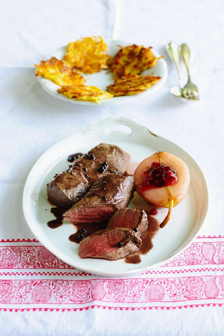 Rare fillet of venison in elderberry sauce served with steamed pears and cranberries