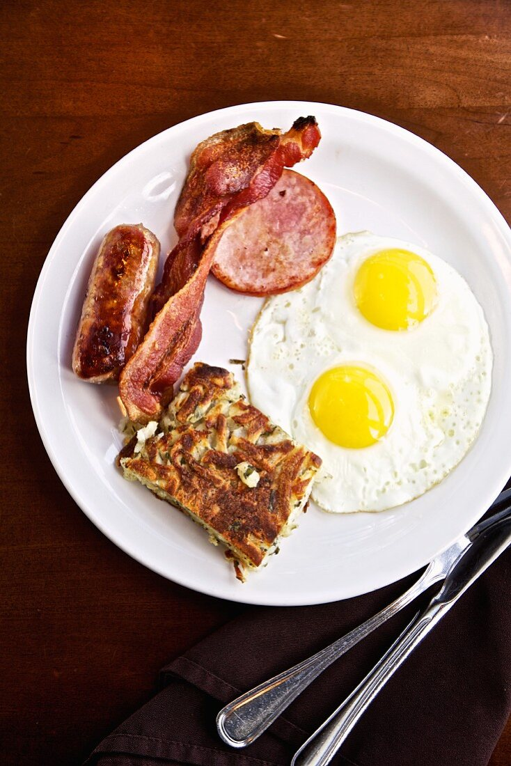 American breakfast with two fried eggs, bacon and sausage