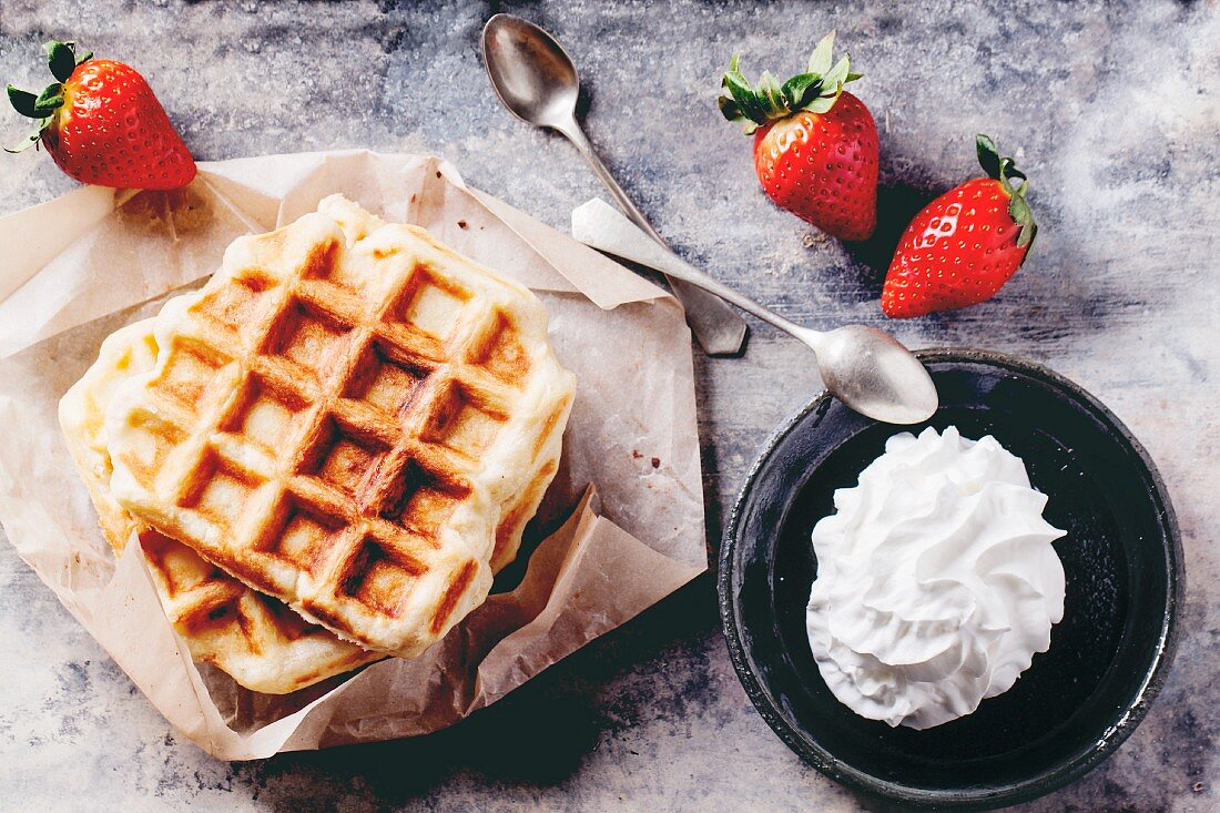 Belgian waffles served with strawberries and whipped cream