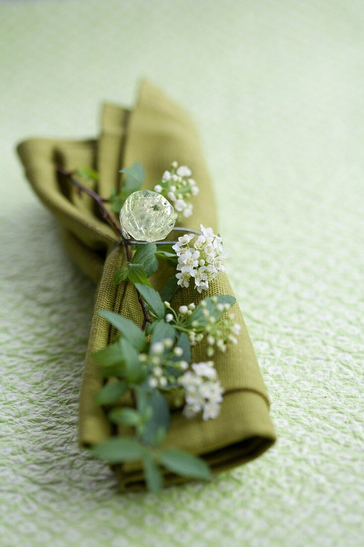 A napkin decorated with flowers and a rhinestone