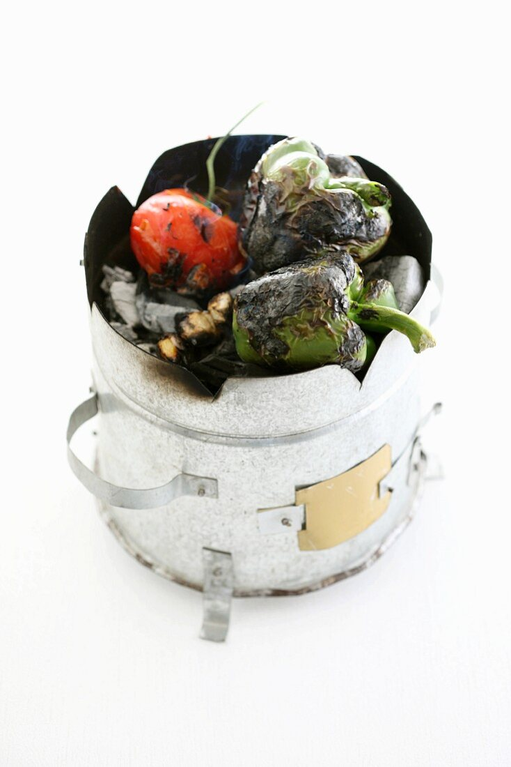 Grilled peppers and a tomato on coals in a barbecue oven