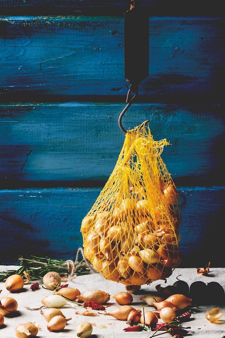 A string bag of small onions against a wooden wall