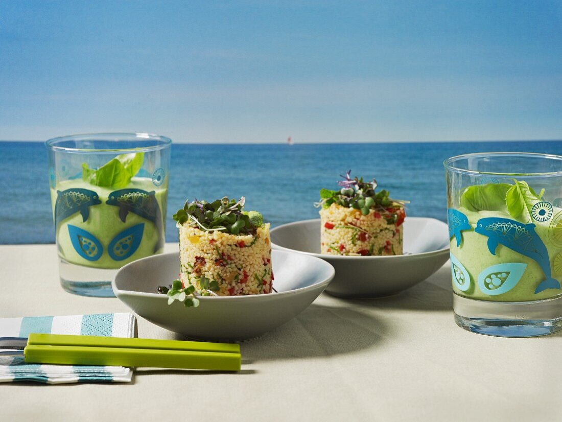 Couscous timbale and iced pea soup on a table overlooking the sea