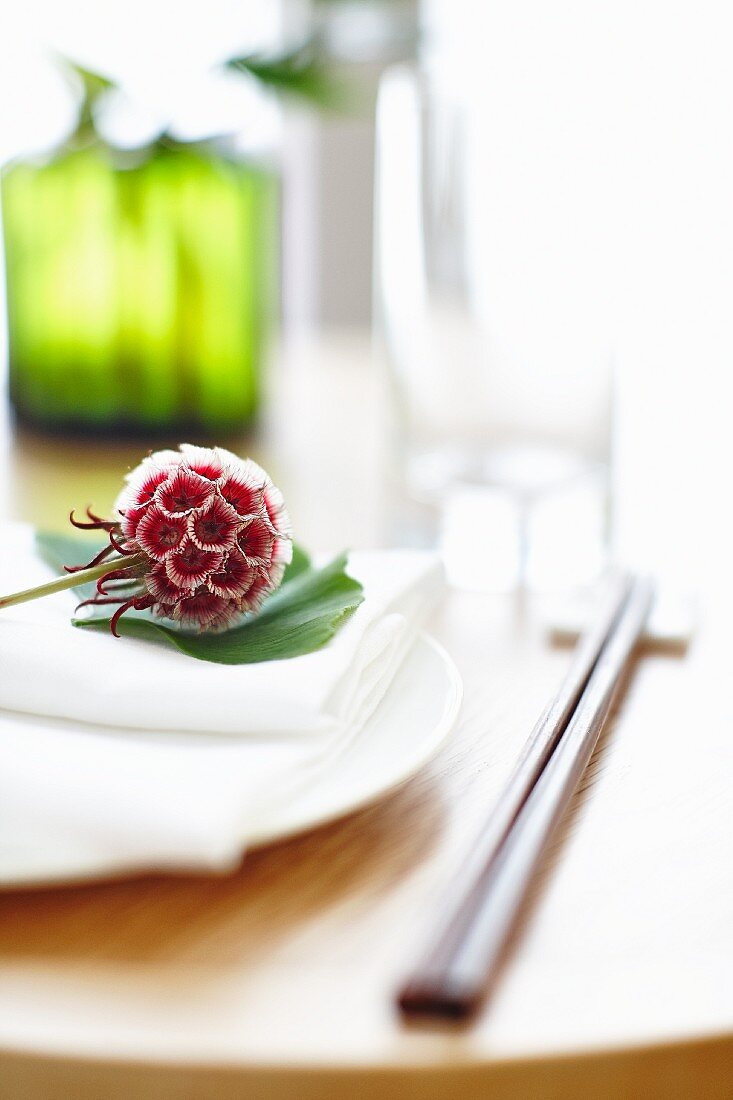 A flower on a ginkgo leaf on a place setting (Asia)