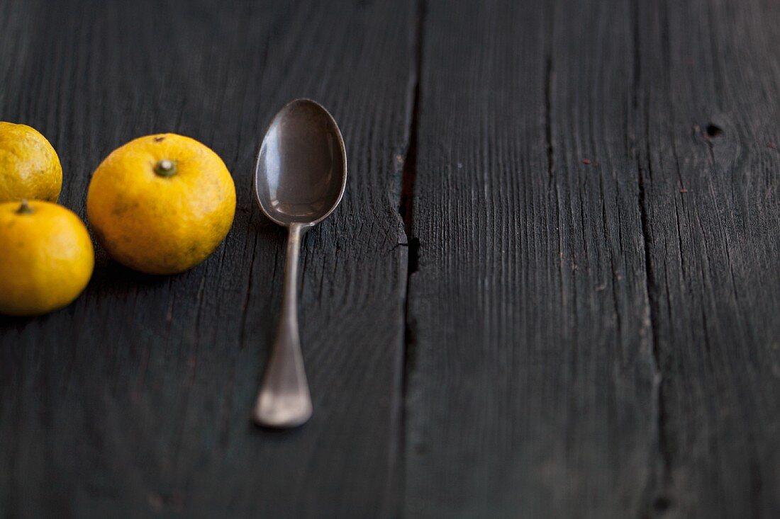 Three yuzu fruits on a wooden surface