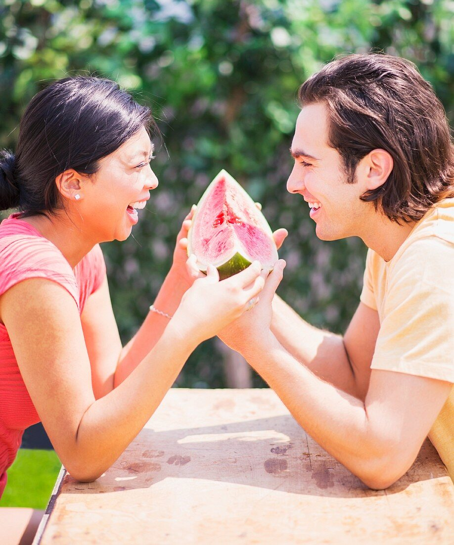 A couple eating a watermelon together