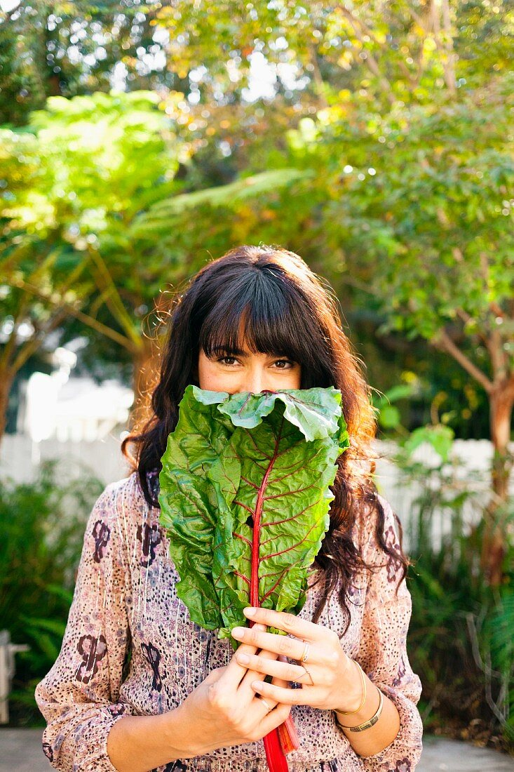 A young woman holding a red chard leaf in a garden