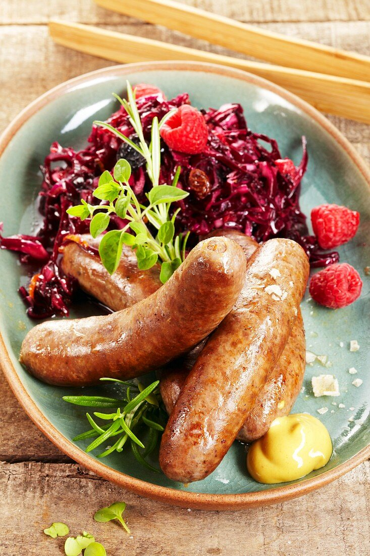 Wild boar sausages with red cabbage and raspberries