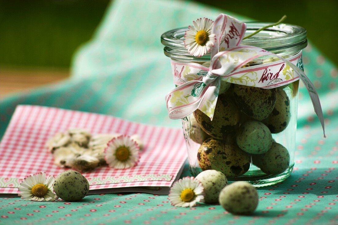 Quail's eggs in a jar decorated with daisies and a bow