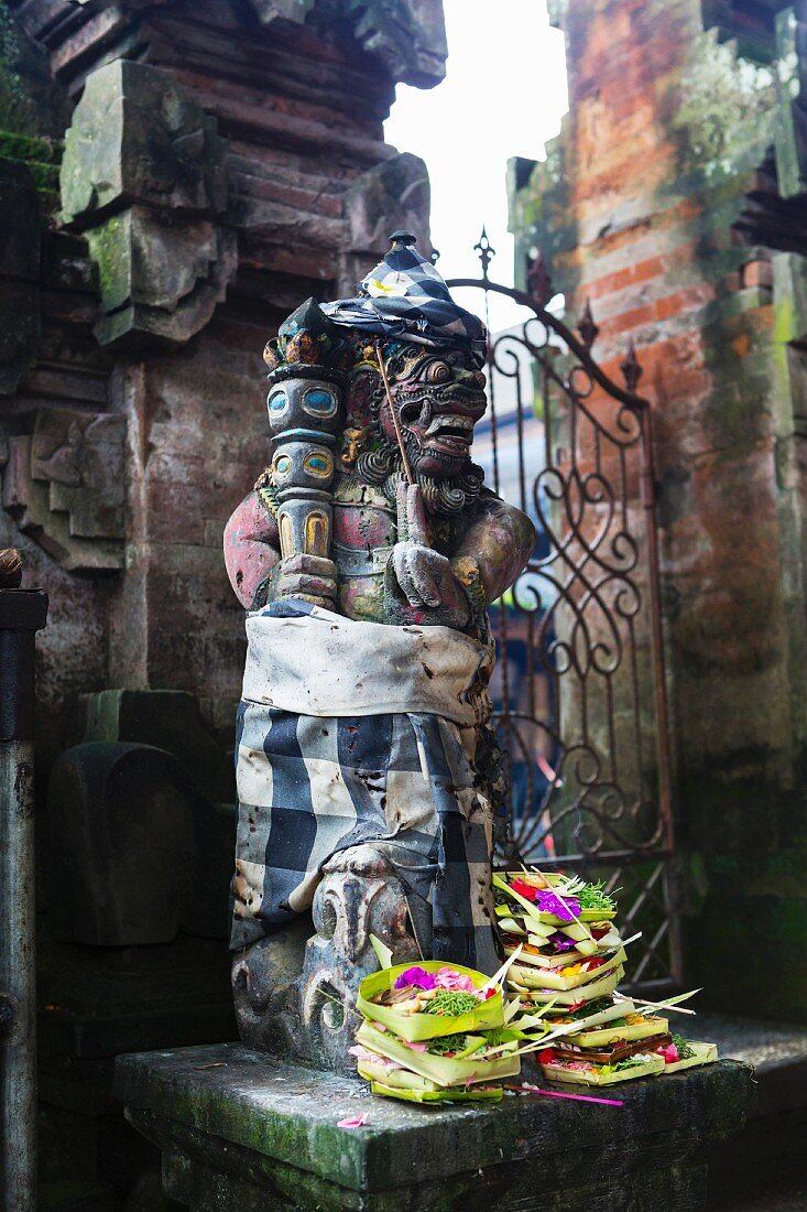 Offerings at the foot of a Hindu statue in Ubud, Bali, Indonesia