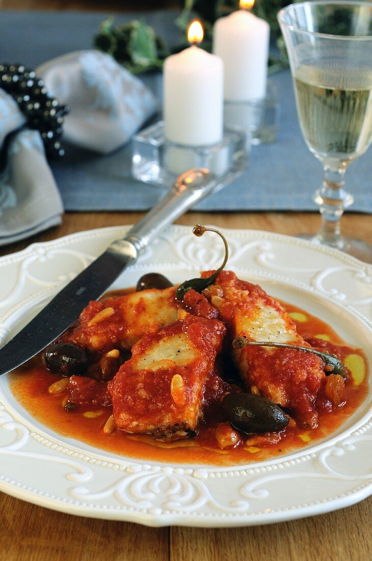 Stockfish in tomato sauce with raisins, pine nuts and capers