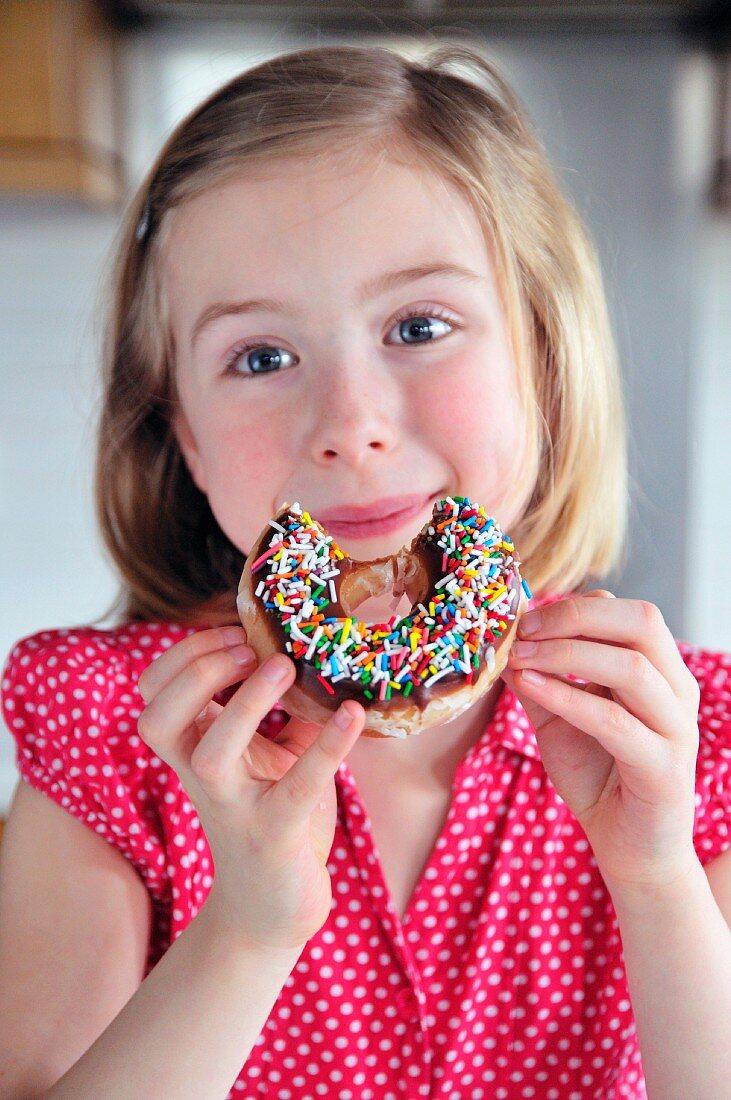 A little girl eating a doughnut with sugar sprinkles