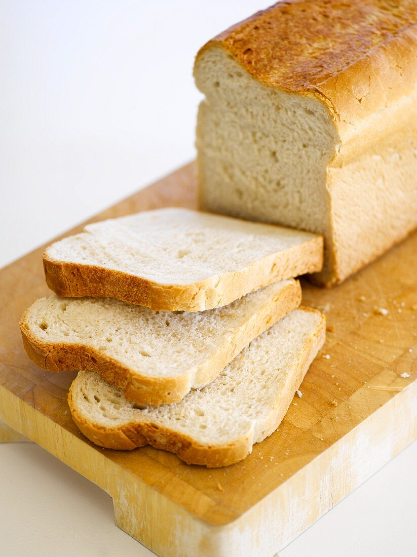 A sliced loaf of bread on a chopping board