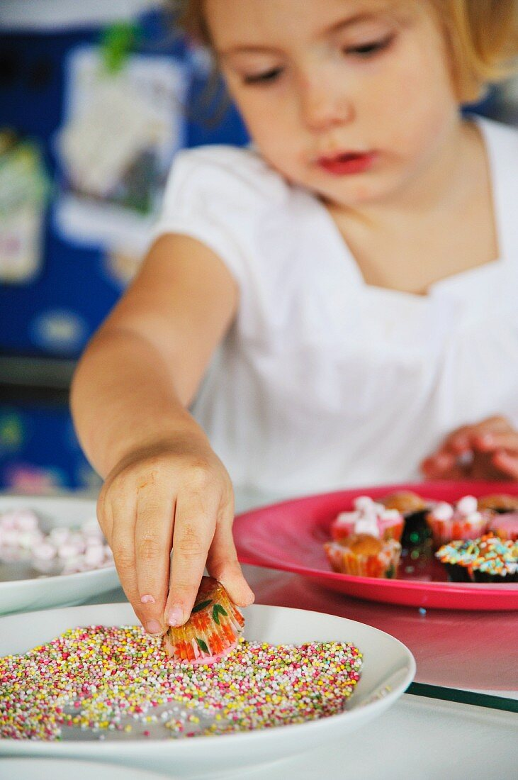 A little girl decorating mini muffins with sugar pearls