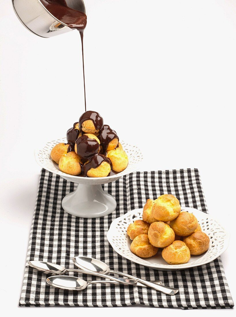 Chocolate sauce being poured over profiteroles