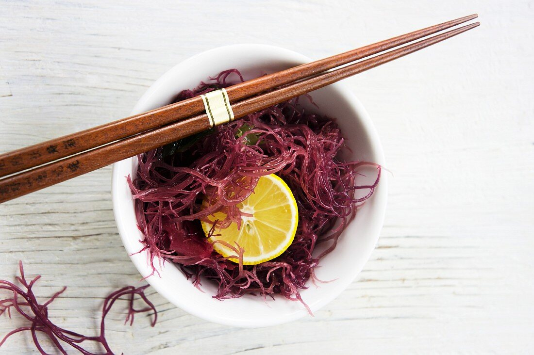 Red seaweed with yuzu slices in a white bowl with chopsticks