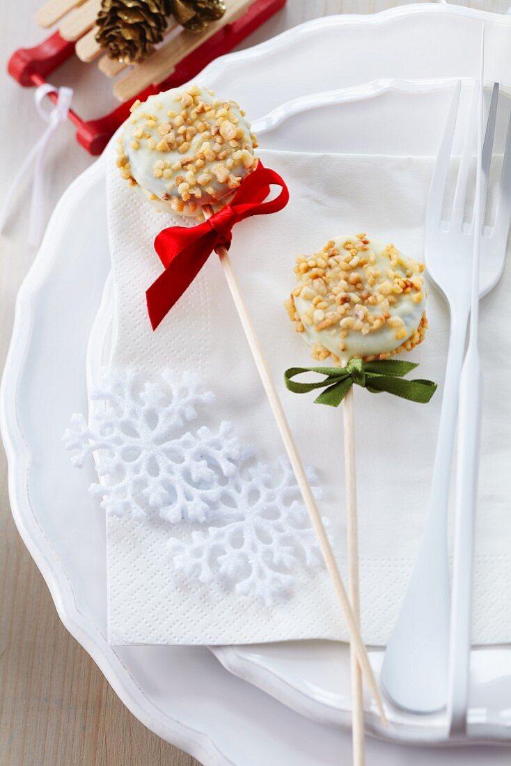 Zwei weihnachtliche Cake Pops mit weisser Kuvertüre und Nusskrokant