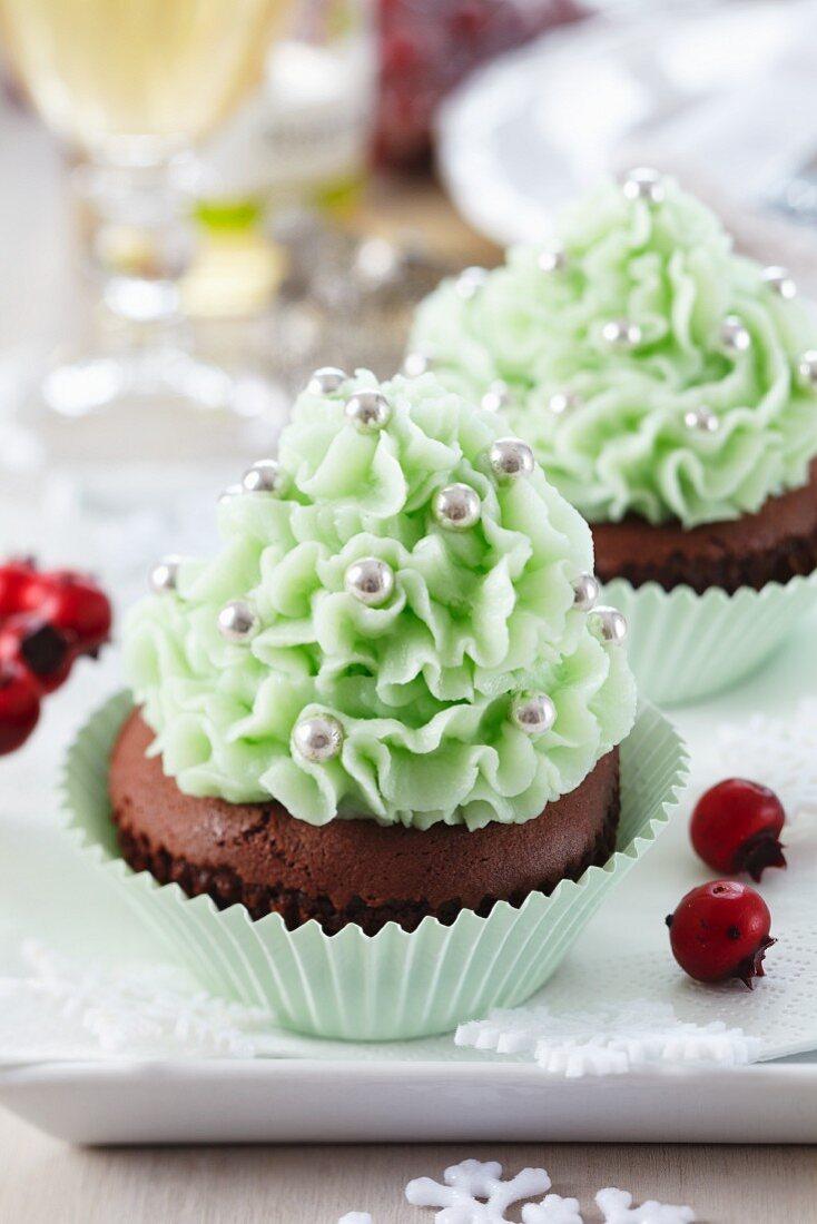 Weihnachts-Cupcakes mit mintfarbener Creme und silbernen Zuckerperlen