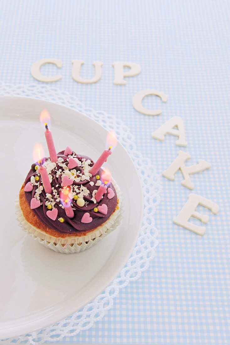 A cupcake for a birthday with letters spelling out the word 'cupcake'