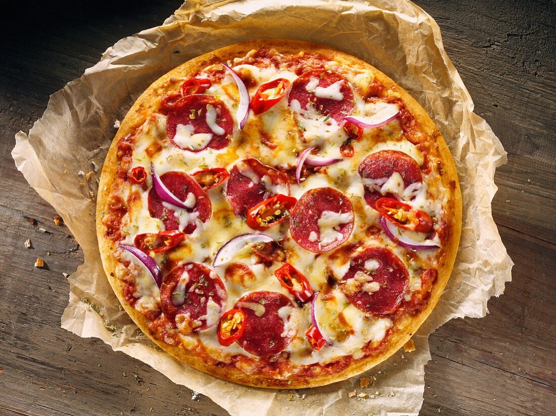 Salami pizza with onions and chilli peppers on a piece of baking paper