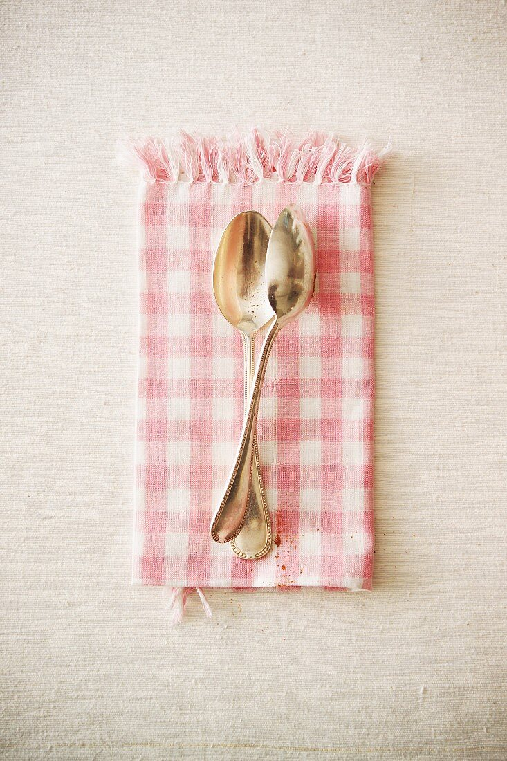 Two dessert spoons on a checked cloth