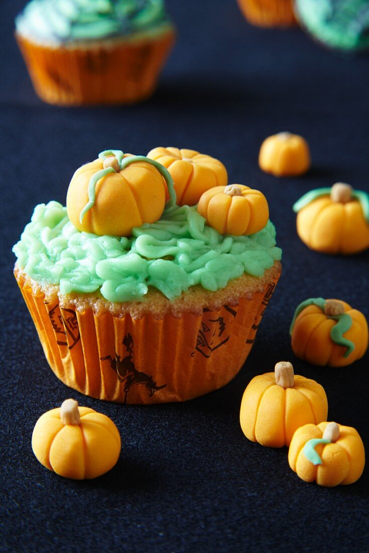 A cupcake decorated with marzipan pumpkins for Halloween