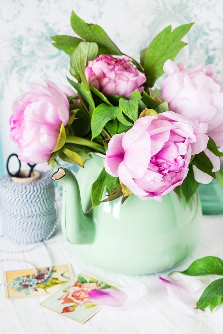 A bunch of pink peonies in a green metal jug against a wallpapered wall