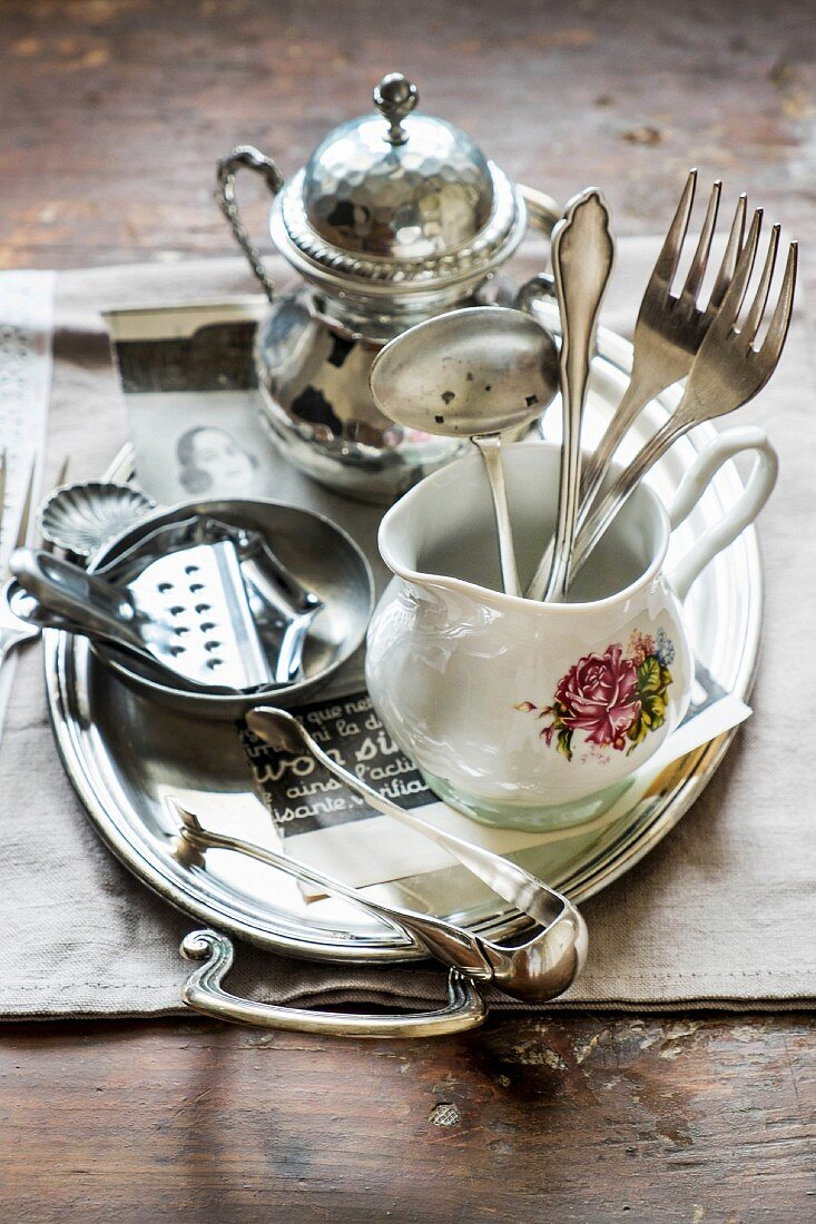 Silver cutlery in a porcelain jug and a lemon press on a tray