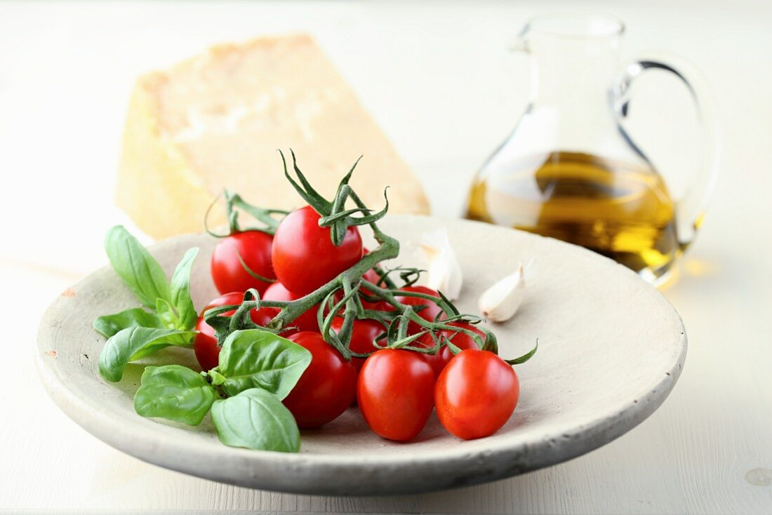 Tomatoes on a stone plate with basil and garlic with a jug of oil and a block of Parmesan in the background