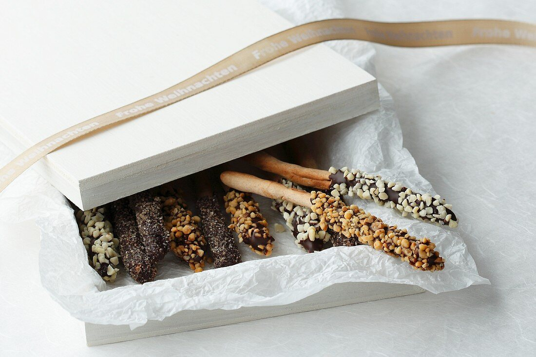 Decorated cinnamon sticks in a white box with tissue paper and a ribbon (Happy Christmas)