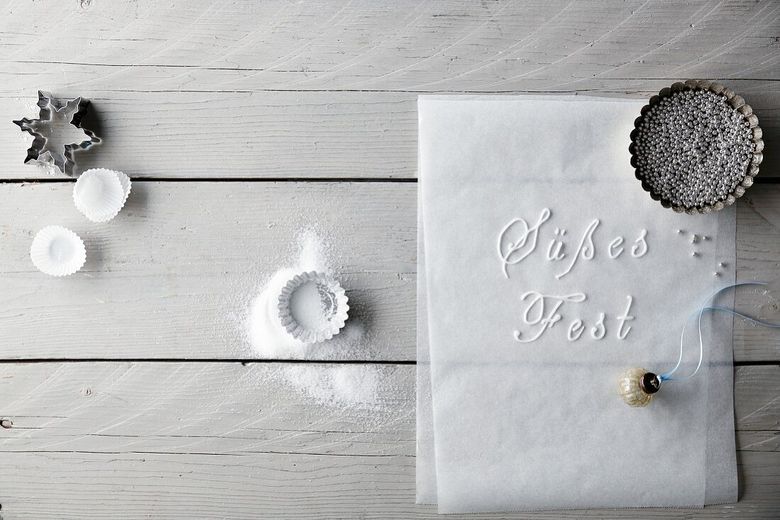 Baking tins, cutters, decorative pearls, a bauble and German words written on baking paper