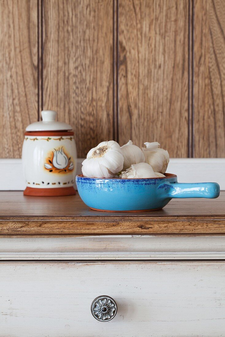 Garlic bulbs in a blue ceramic bowl