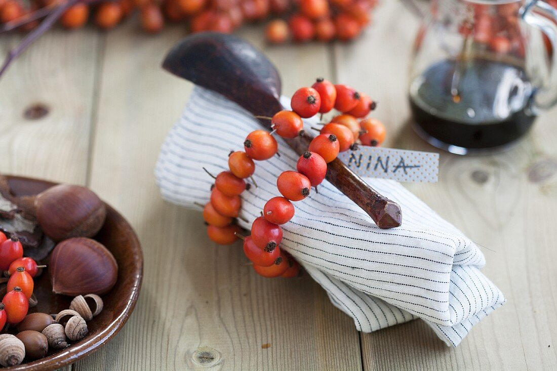 A napkin and a wooden spoon wrapped with a rosehip wreath with a nametag