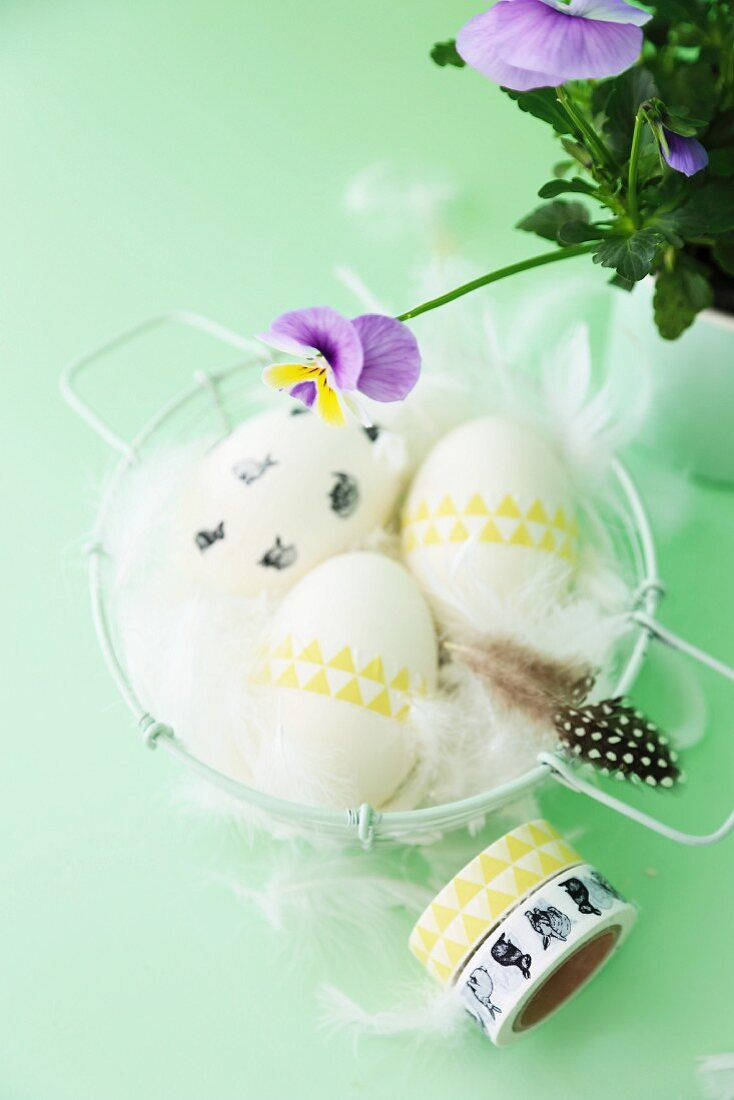 Easter arrangement; eggs decorated with washi tape and feathers in basket