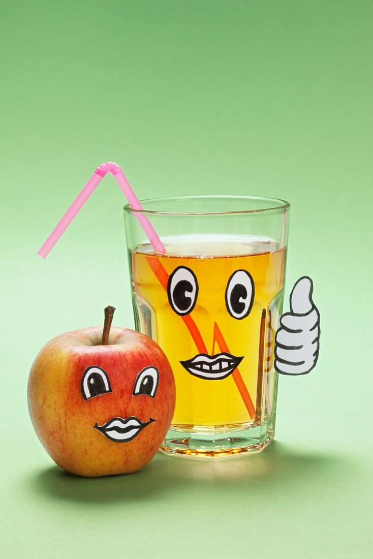 An apple and a glass of apple juice a face