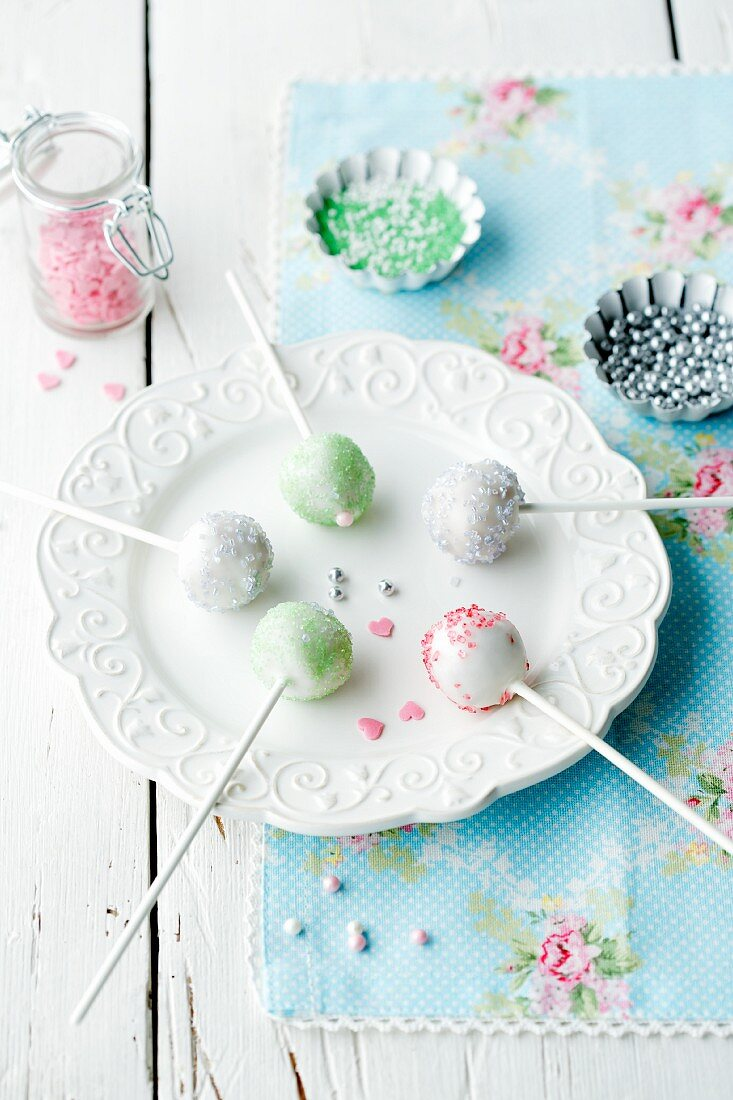 Five different cake pops on a plate with sugar pearls in the background